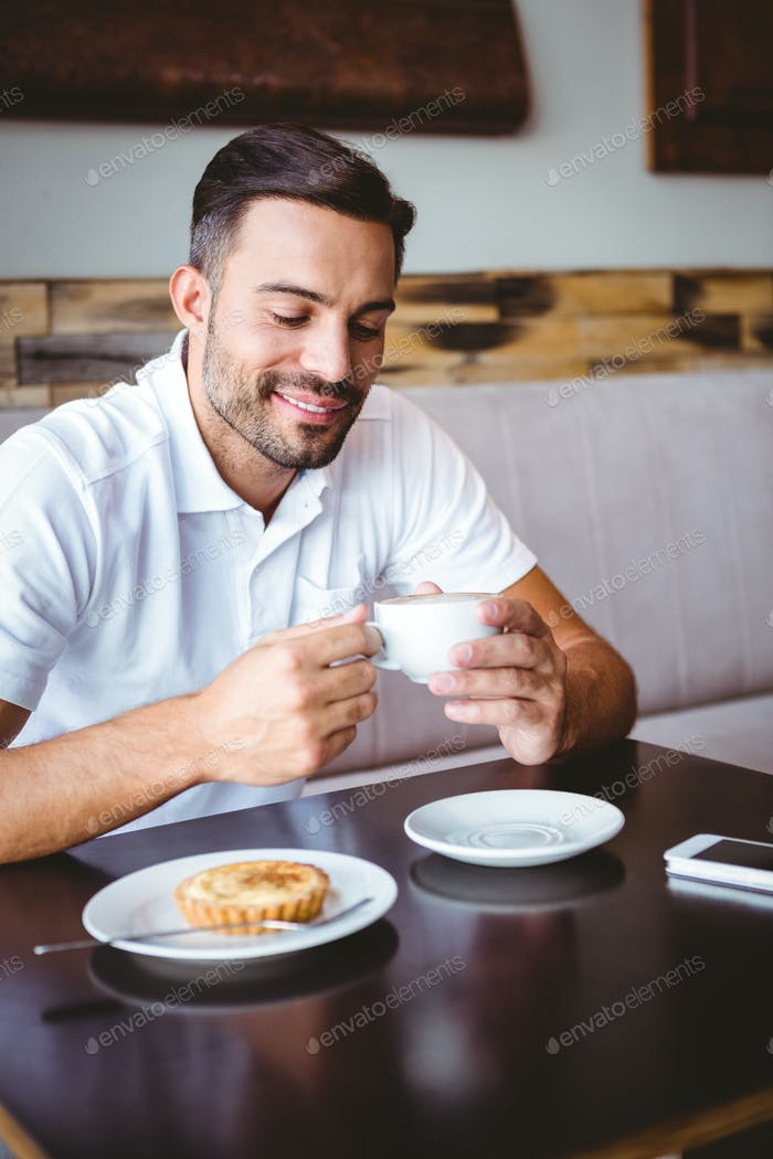 Young man drinking cup of coffee and pastry beside at the cafe