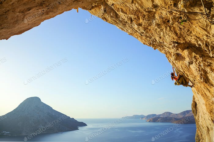 Young woman climbing challenging route in cave