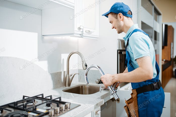 Plumber in uniform changes faucet in the kitchen
