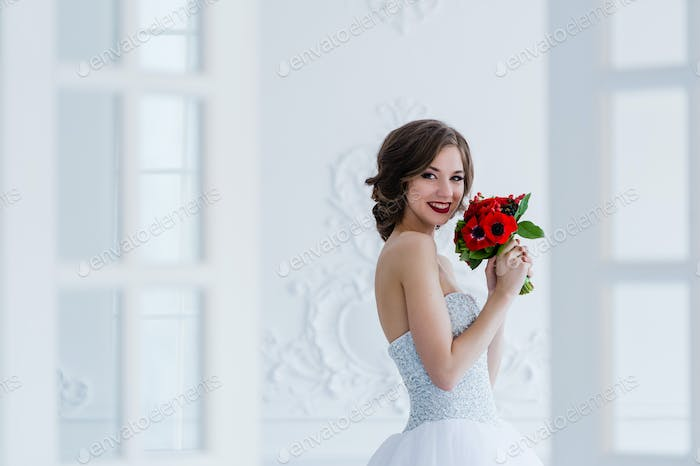 Gorgeous bride poses in the bright room. Light fashion photo in cold colors.