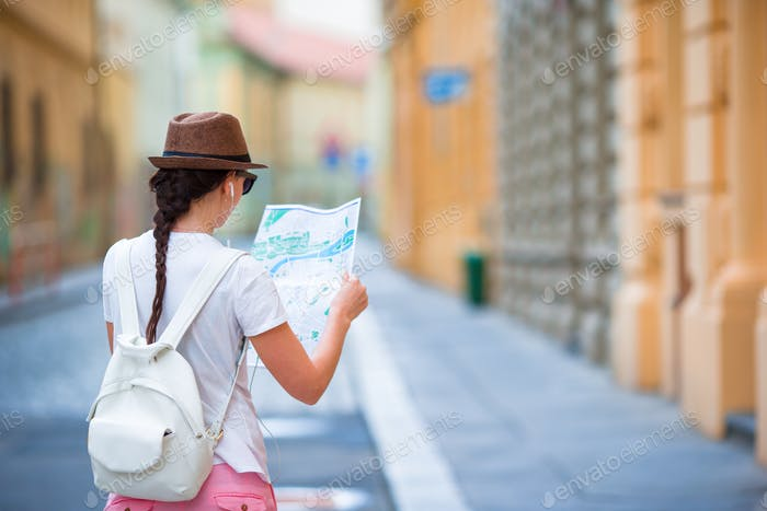 Happy young woman with a city map in city. Travel tourist woman with map in Prague outdoors during