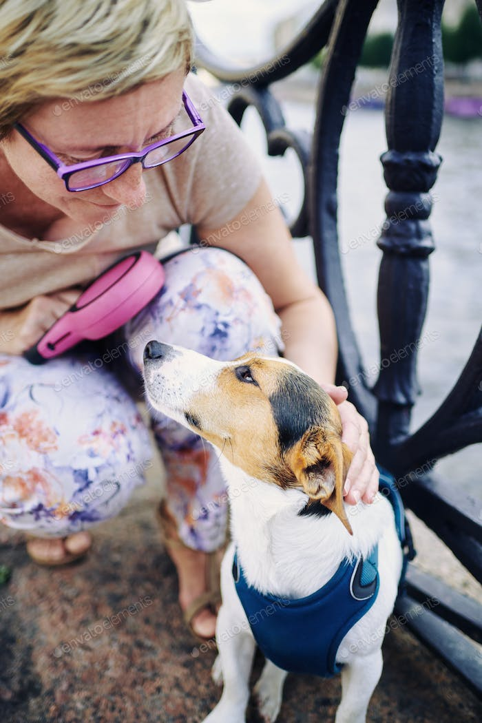 Senior woman petting dog on embankment