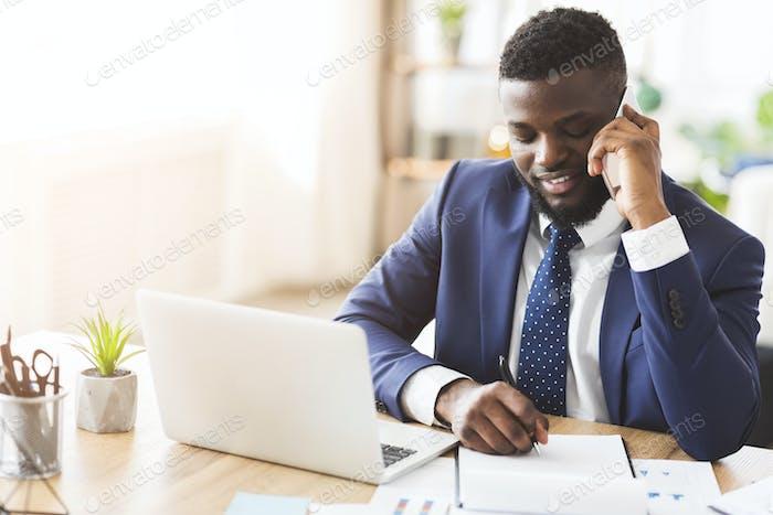 Lächelnder Geschäftsmann telefonisch mit Sekretärin, Notizen aufschreiben