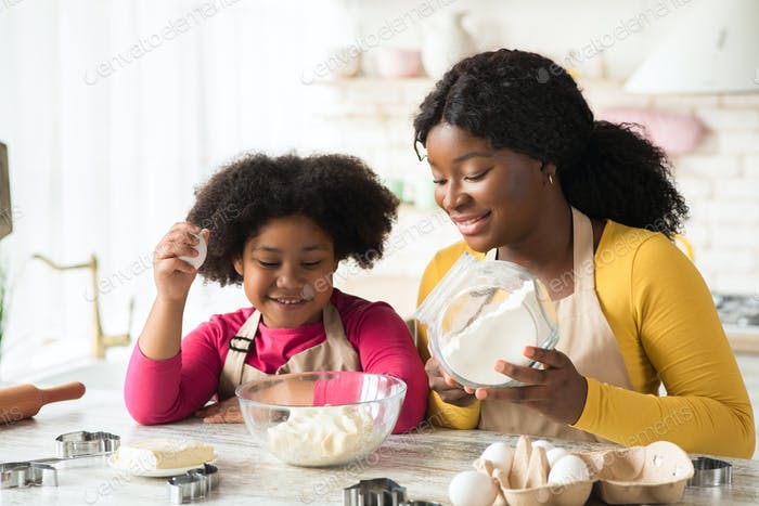 Cheerful black mother and little daughter preparing dough in kitchen together