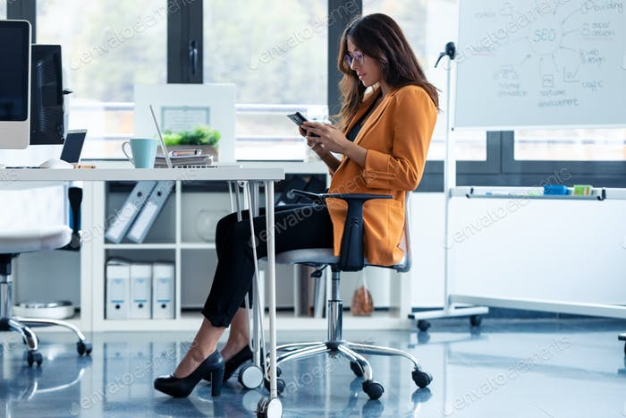 Business young woman using her mobile phone while sitting in the office.