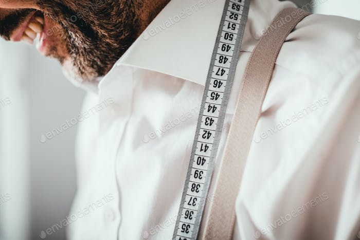 Close up of measuring tape on professional tailor neck who working in sewing workshop