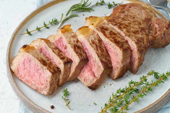Keto ketogenic diet beef steak, striploin on gray plate on white background