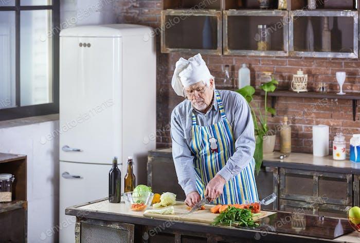 Senior man in chef hat chopping fresh vegetables for salad