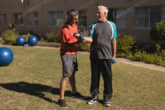 Front view of trainer assisting senior man in performing exercise with dumbbells in the park
