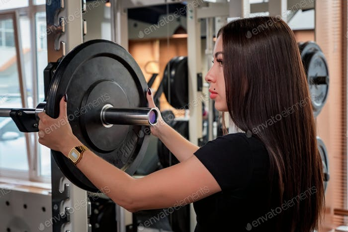 Fitness woman puts plate on barbell side view