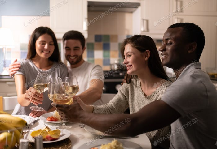 Diverse couple proposing toast to friends