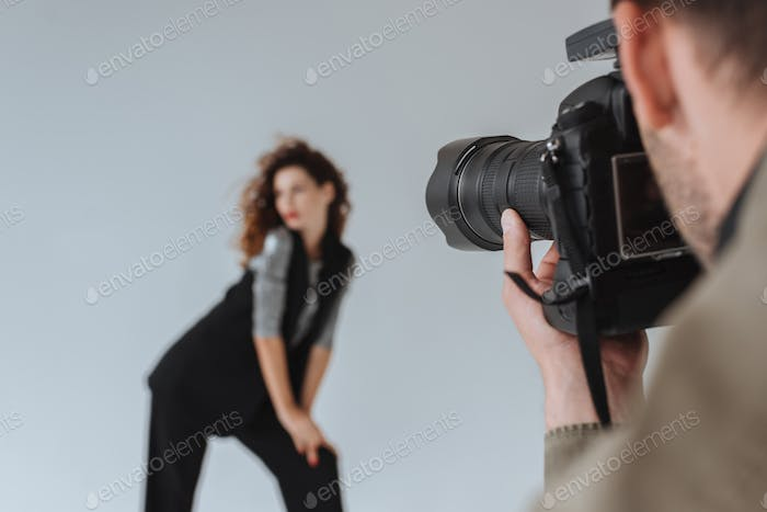 professional photographer and beautiful model on fashion shoot in photo studio