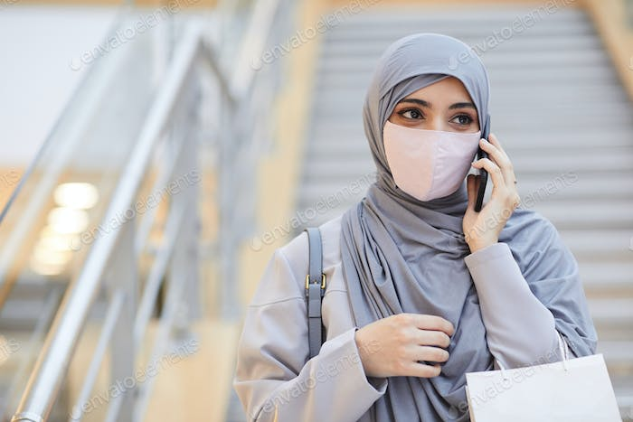 Middle-Eastern Woman Speaking by Smartphone in Shopping Mall