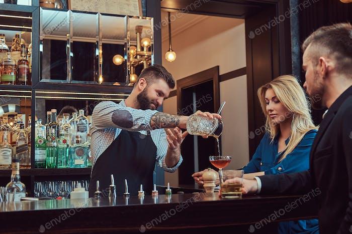 Stilvoller brutaler Barmann serviert ein attraktives Paar, das einen Abend auf einem Date verbringen.