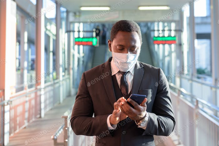 Portrait of African businessman with mask using phone at the train station outdoors