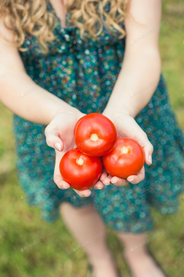 Blonde woman holding some home grown organic tomatoes