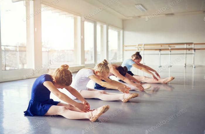 Girls performing ballet sitting and bending in class