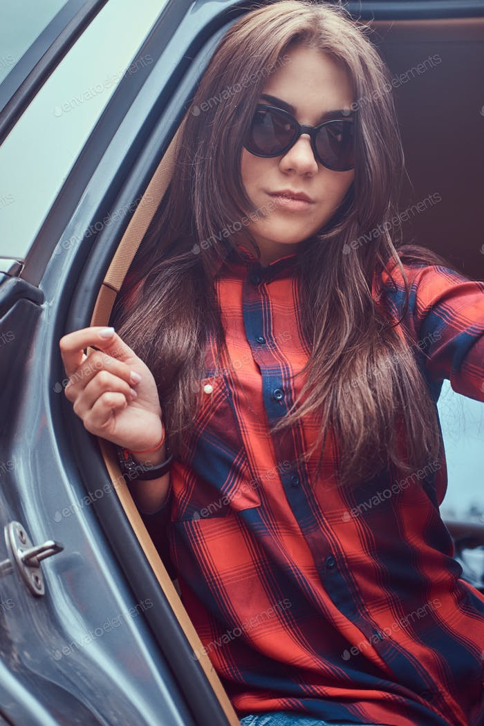 Portrait of a Caucasian woman in a flannel shirt and sunglasses
