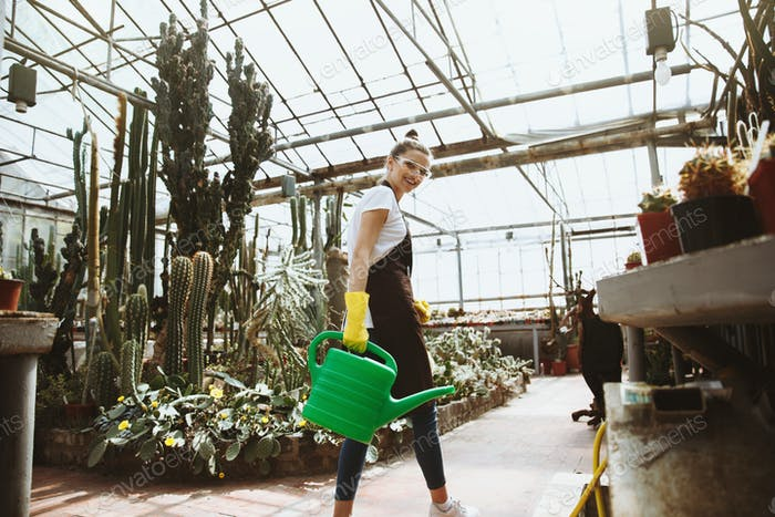 Happy young lady in glasses standing in greenhouse