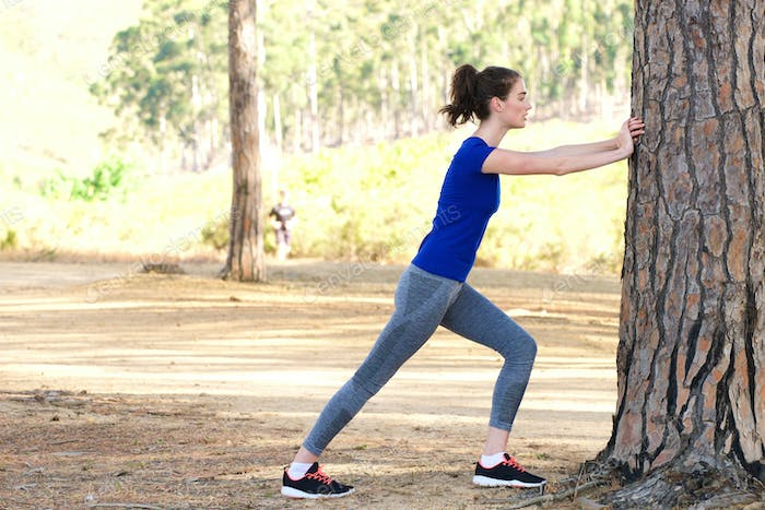 Sporty woman pushing against tree