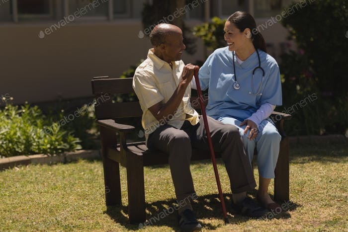 Young smiling doctor talking with happy senior man on bench on sunny day in garden