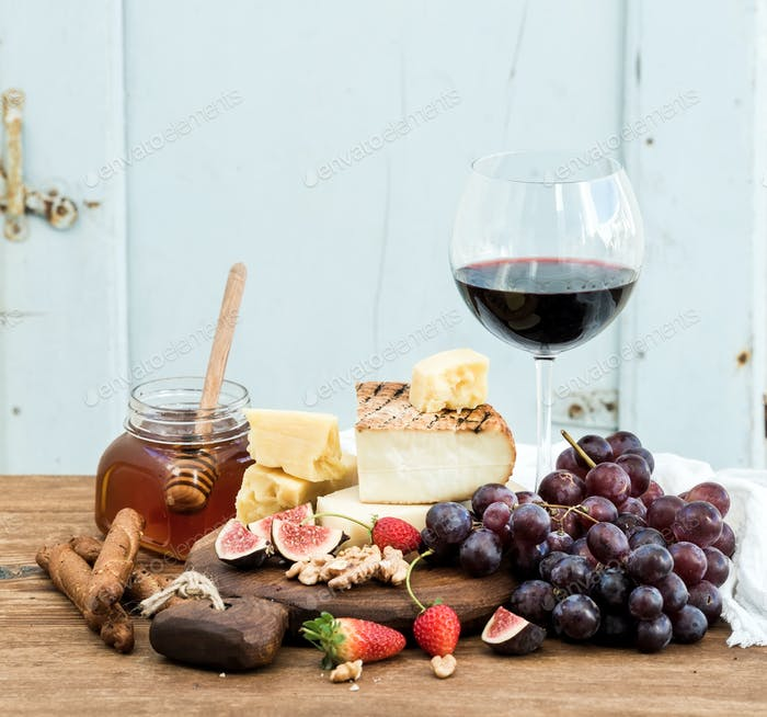 Glass of red wine, cheese board, grapes,fig, strawberries