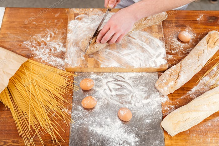 Wooden table of baker cutting fresh bread on the kitchen