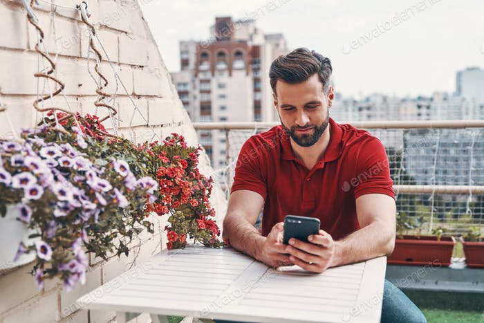 Handsome young man in casual clothing using smart phone while sitting on the rooftop patio