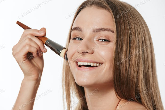 Beauty portrait of young half-naked woman applying makeup with brush