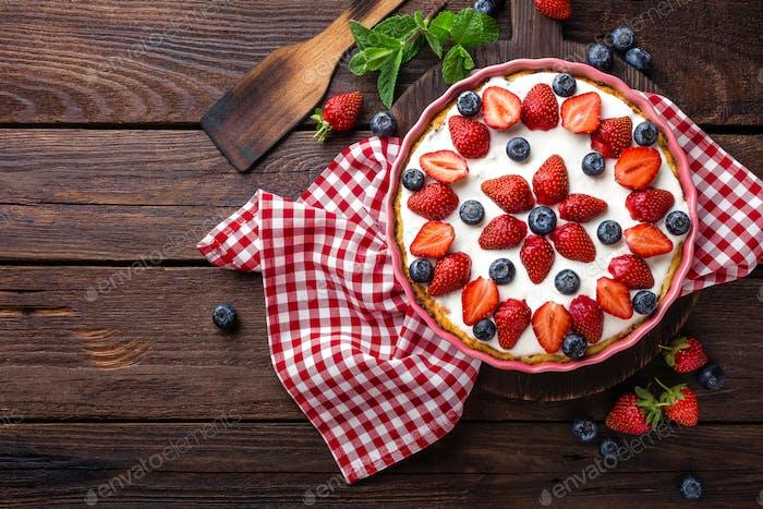Köstliche Erdbeerkuchen mit frischer Heidelbeere und Schlagsahne auf rustikalem Holztisch, Käsekuchen