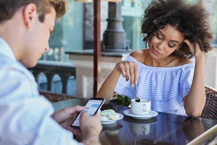 Young woman bored while her boyfriend using mobile phone
