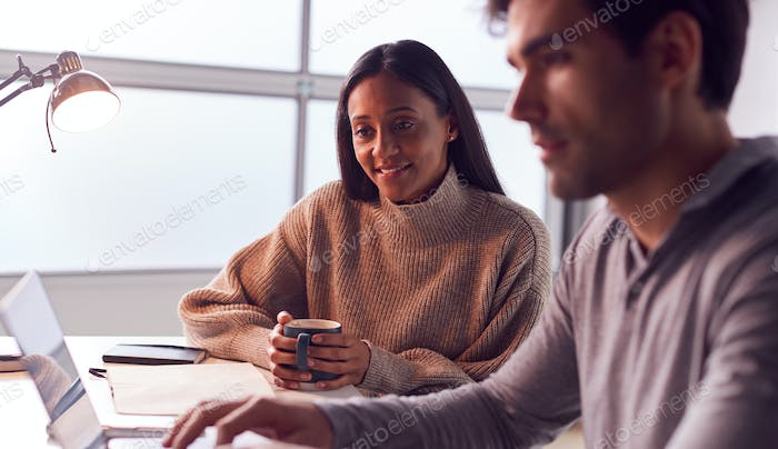 Businessman Working On Laptop At Desk Collaborating With Female Colleague Drinking Coffee