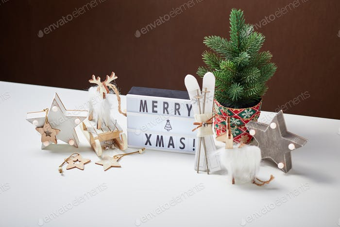 Light box inscription Merry Xmas and wooden ornaments