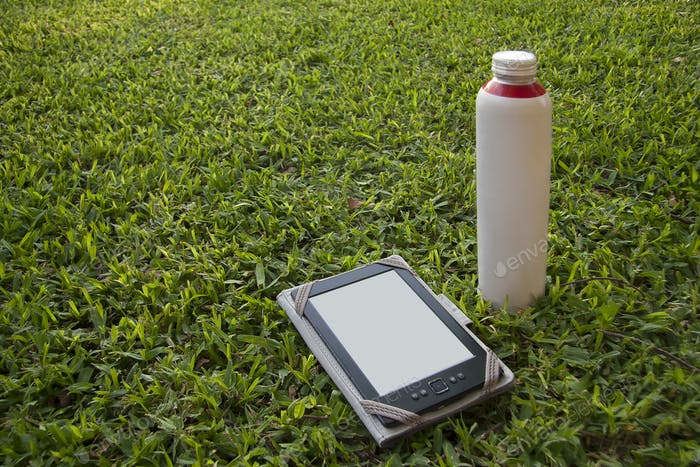 An electronic book reader and a thermos bottle on the grass