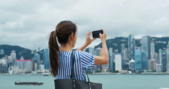 Frau Nutzung des Mobiltelefons, um Foto in Hong Kong Stadt zu nehmen