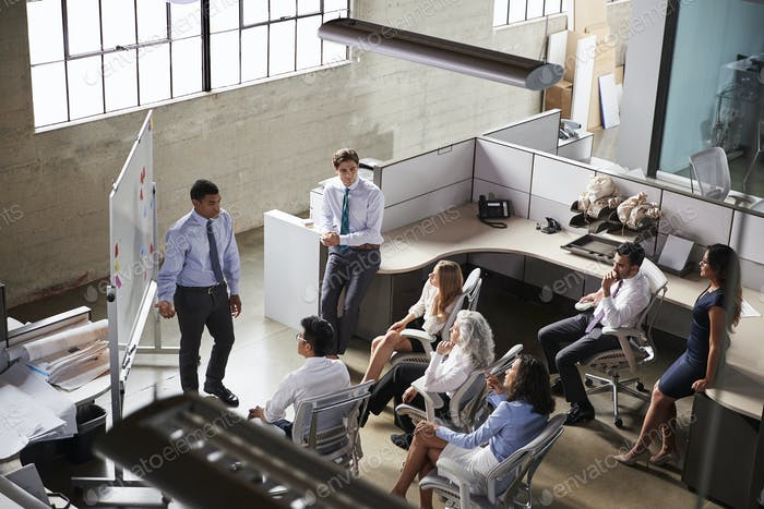 Businessman giving presentation to colleagues, elevated view