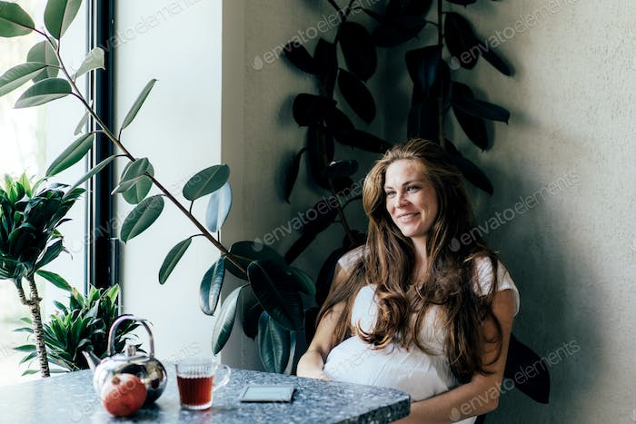Laughing charming pregnant woman at a table in a cafe.