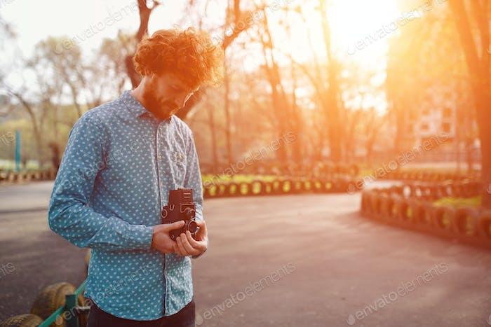 Der rothaarige Kerl hält eine Mittelformat-Filmkamera in seinen Händen
