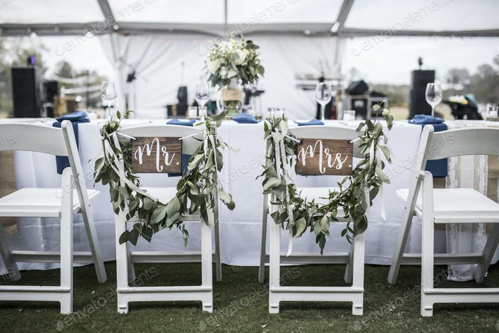 Wedding table under tent, with Mr and Mrs signs on the chairs