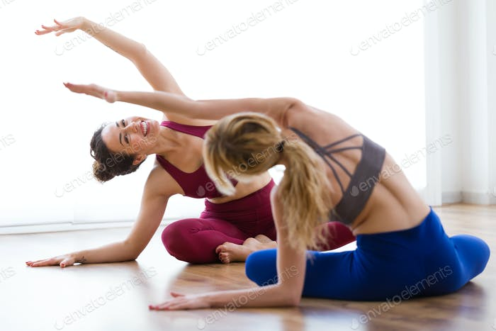 Two pretty young women practicing yoga at home.