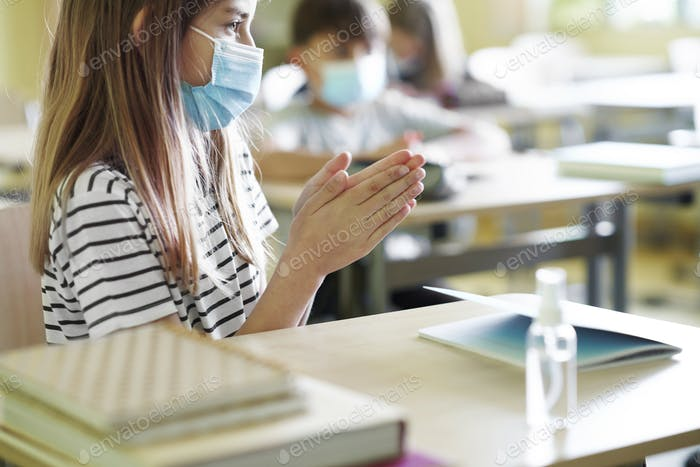 Close up of girl disinfects hands in class