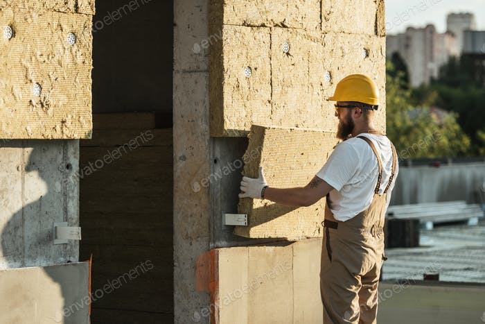 side view of builder in protective helmet and googles doing insulation of wall at construction site