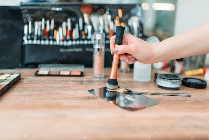 Make up artist hand with brush prepares cosmetics