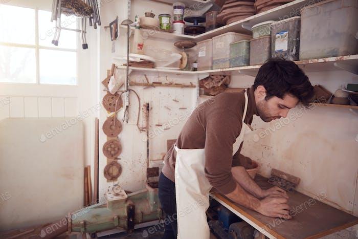 Male Potter usando delantal desplegar un trozo de arcilla en el estudio de cerámica