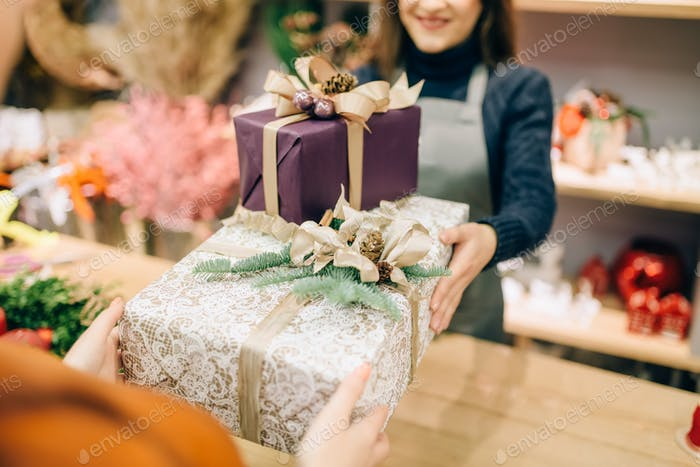 Wrapping service seller gives to customer gift box