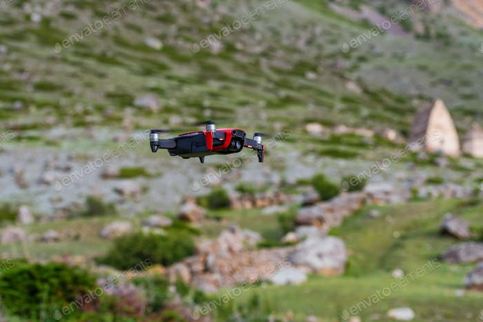 Moderne dunkle und rote Drohne in der Luft in Bergen in der Nähe
