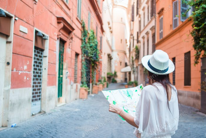 Happy young woman with a city map on desert street in Europe. Travel tourist woman with map in Rome
