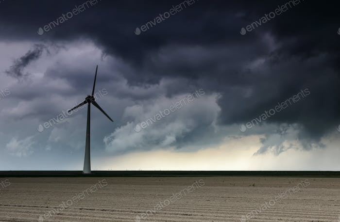 dark storm cloud over windturbine and field