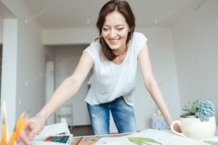 Glückliche Frau Malerin arbeiten in Kunst Studio