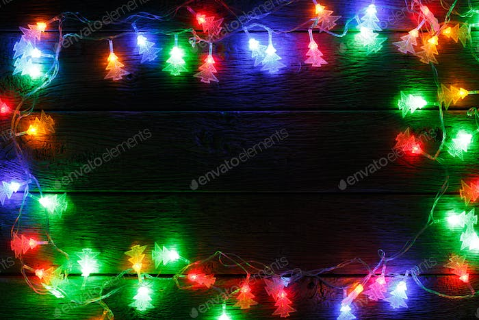 christmas lights border on black wood background